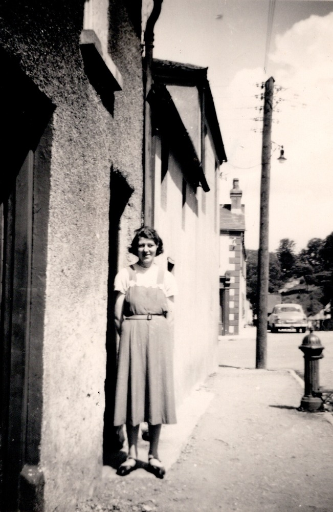 Greta Carley  at door beside water tap.png